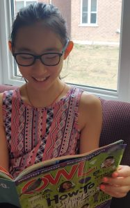 young girl reading a nature book